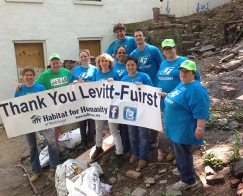 People holding sign which reads Thank you Levitt Fuirst