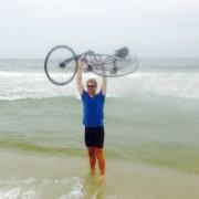man holding bike over head in ocean