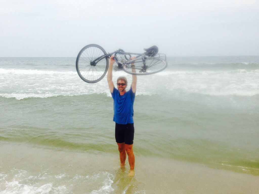man holding bike over head in ocean