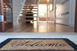 Close up of a welcome mat in front of an inviting house. Focus on foreground