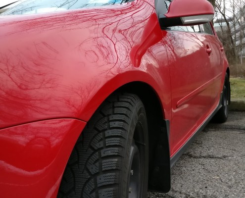 Snow tires on red car